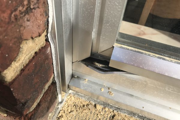 Beschadigd bruut aluminium raam